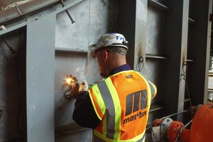 "<div class=""bildtext_en"">1 Technicians drill through the outer wall, then weld the Core Gate in place</div>"