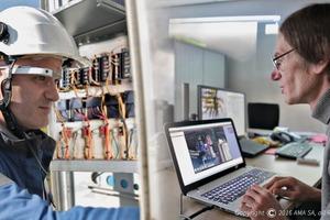 """<div class=""""bildtext_en"""">Using Xpert Eye, an engineer supports an on-site technician working on a switch box </div>"""