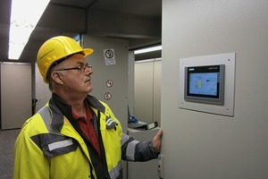 """<div class=""""bildtext_en"""">4 The head of the electrical workshop checking the cement mixtures in front of the touch panel in the control cabinet door. Not only are measured values visualized here, but direct local operation of the loss-in-weight scales is also possible</div>"""