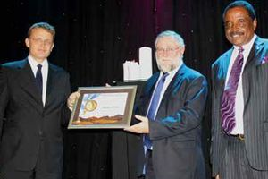 1 Hans-Wilhelm Schuette, receiving the NMA Manufacturer of the Year Award from Hon Calle Schlettwein, Minister of Trade & Industry and Brian Black, Chairperson of the NMA. The company also won the NMA Most Environmentally Friendly Manufacturer Award for 2013